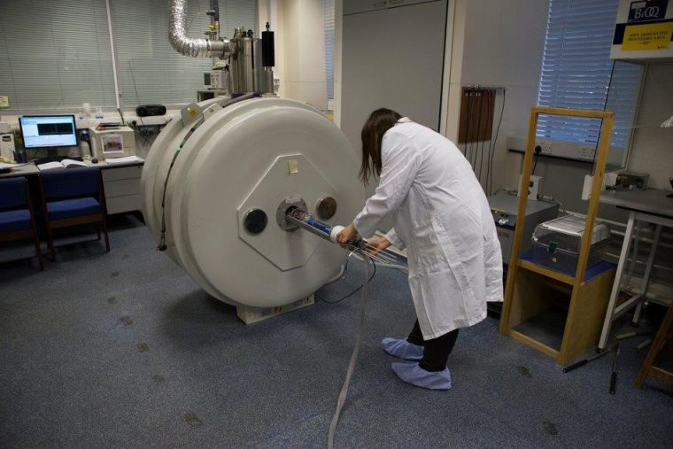 A research assistant operates the Horizontal Bore System