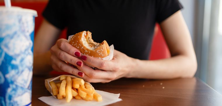 young person eating a burger and chips
