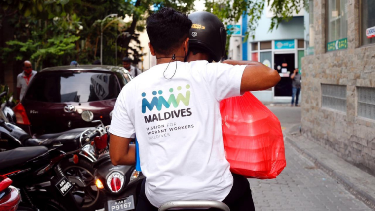 two people on a motorbike with a bag of meal packs. One of them is wearing a t-shirt with the Mission for Migrant Workers logo