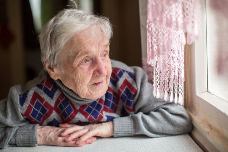 Old woman looking through a window