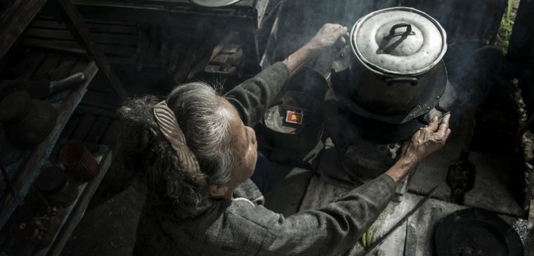 Old Chinese woman cooking on open fire