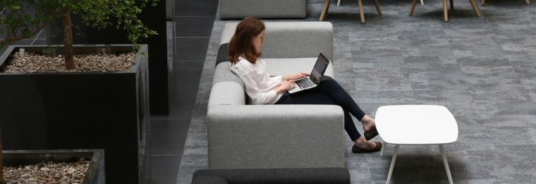 Young woman using a laptop on a sofa in the Big Data Institute building atrium.