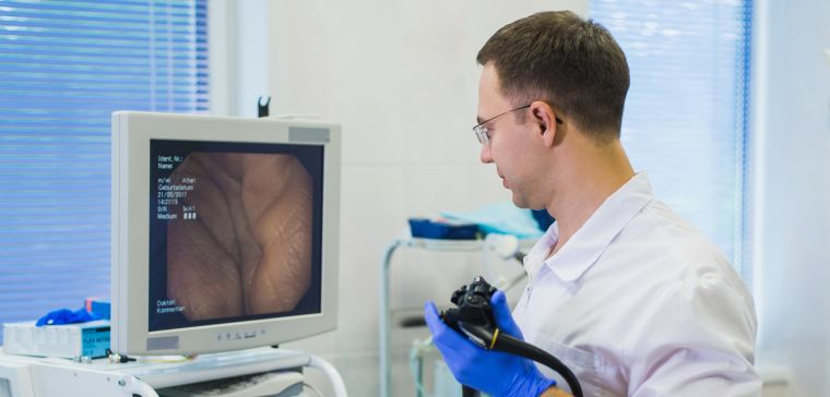 Clinician performing colonoscopy and looking at image on a screen