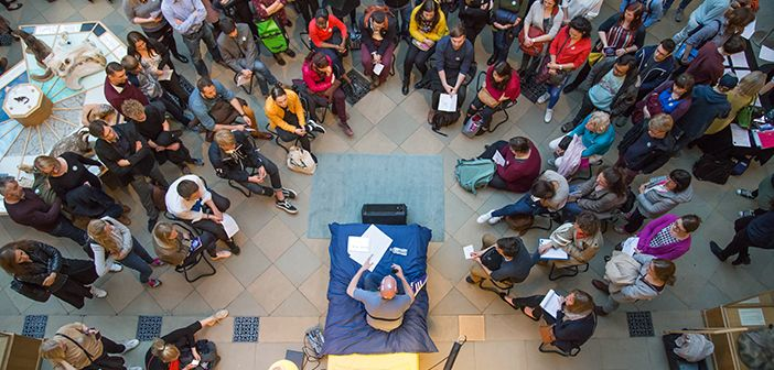 Crowd around a researcher talking from a bed as part of a public engagement activity