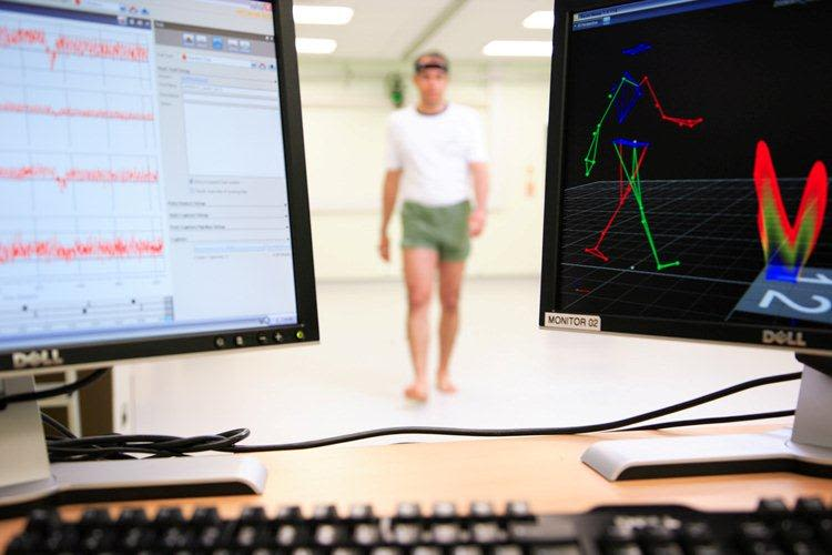 Two computer screens displaying data while a man walks behind.