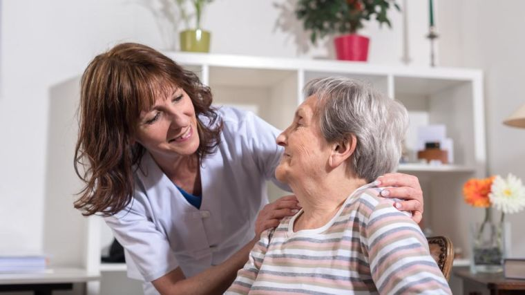 A nurse leans around a patient with her hands places reassuringly on her shoulders.