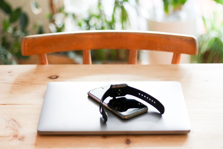 A digital wristwatch on top of a phone on top of a laptop on a table.