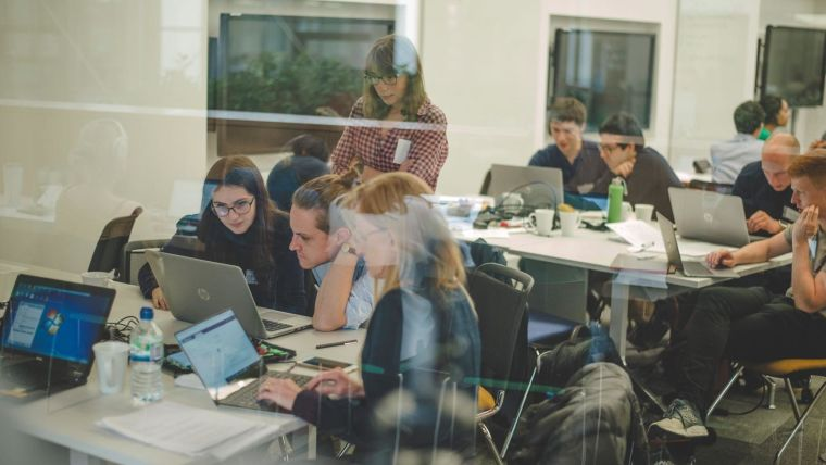 A group of people working on laptops at a DPUK datathon.