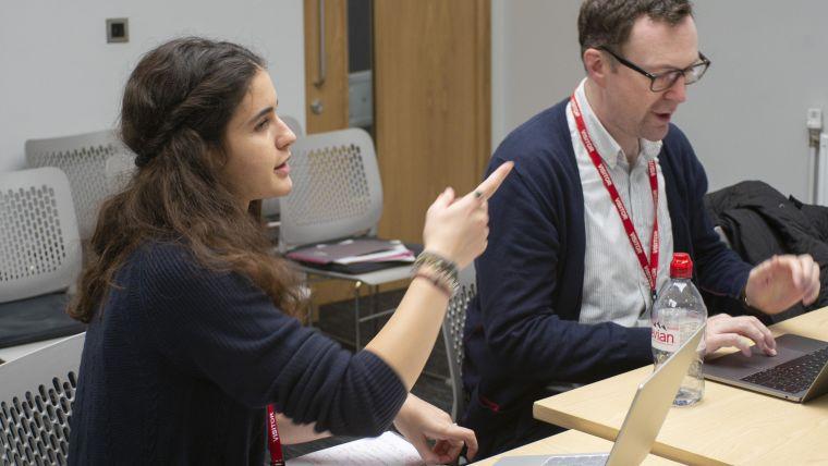 Two participants at a DPUK datathon discuss their ideas.