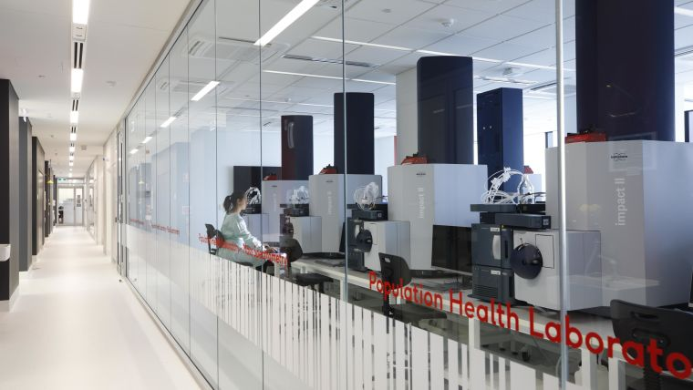 A corridor beside a glass-walled room containing research equipment.