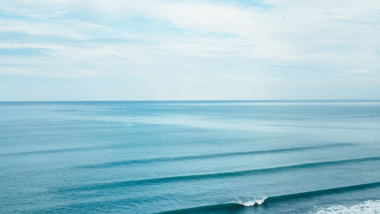 A calm ocean with no waves and a clear sky.