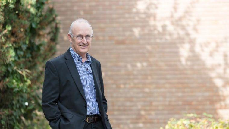 Portrait of Professor John Gallacher standing outside.