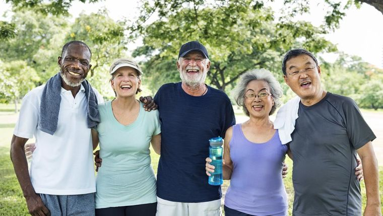 Five people posing for a picture smiling after exercising.