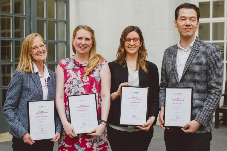 The four Discovery Award winners of 2018 stand holding their certificates.