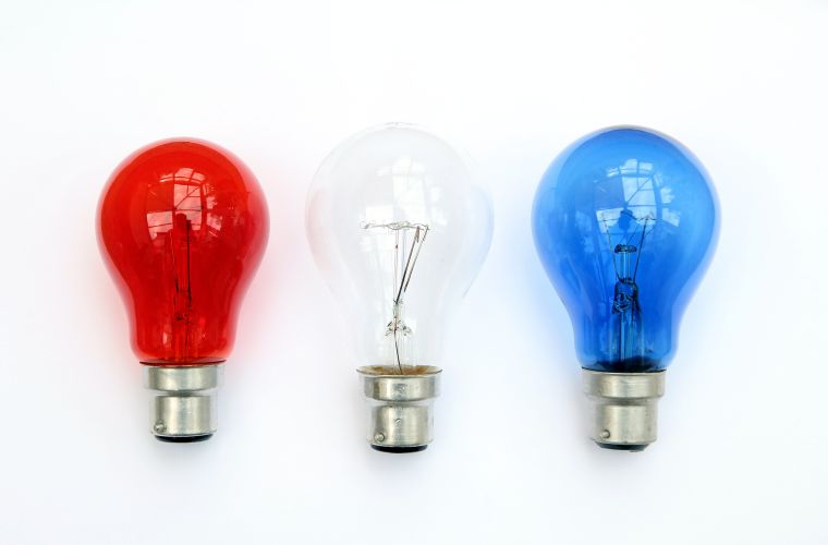 A row of three lightbulbs: one red, one white and one blue.