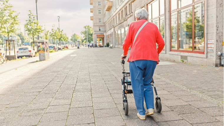 Unrecognizable Senior old woman walking alone with walker on the city street, elderly and disability concept