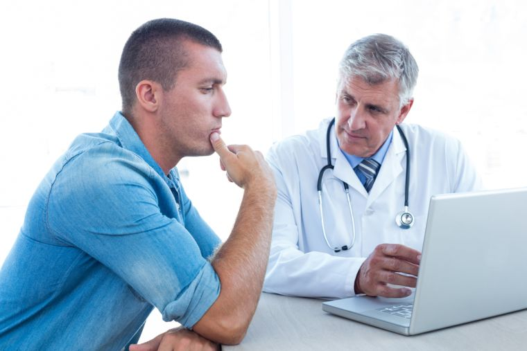 A doctor with a patient and a laptop