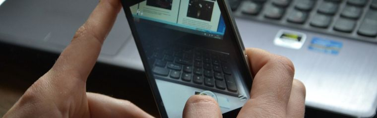 A mobile phone taking an image of a laptop