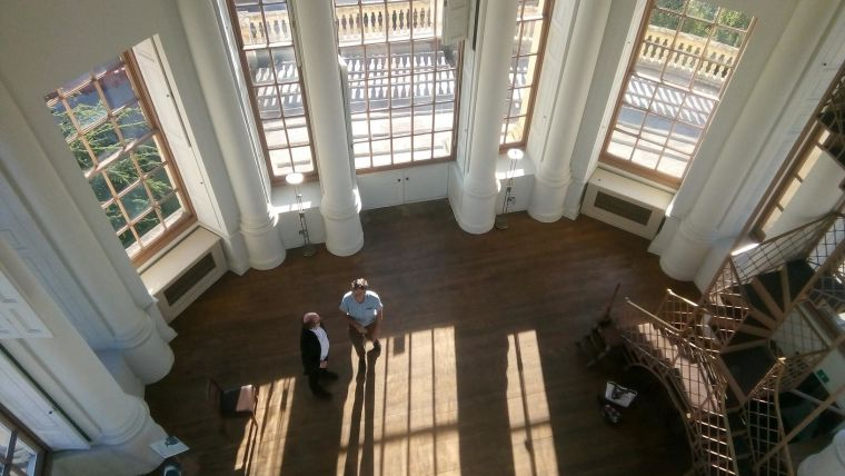 Looking down inside the Radcliff Observatory building at two people talking