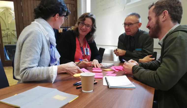 A group of 4 people discussing and planning a public engagement activity