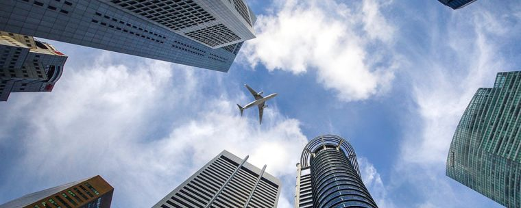 An aeroplane flying above skyscrapers