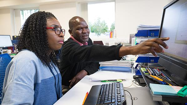 A Black man wearing a black jumper and a Black woman wearing glasses and a blue top sit at a computer in a large open-plan office. They are looking at the screen and discussing something on it, as the man points to it.