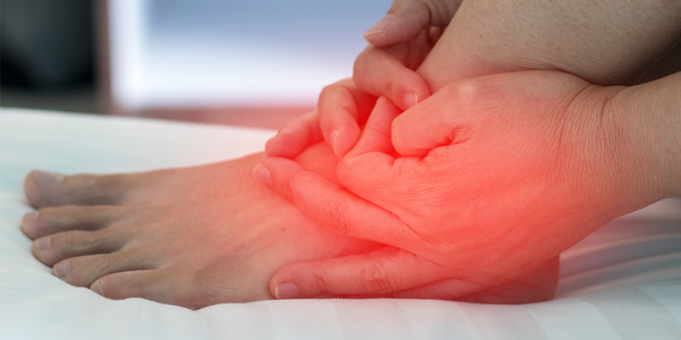 Hands holding a foot with the ankle coloured red to show a sprain