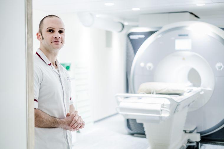 Radiologist stood beside a scanning machine