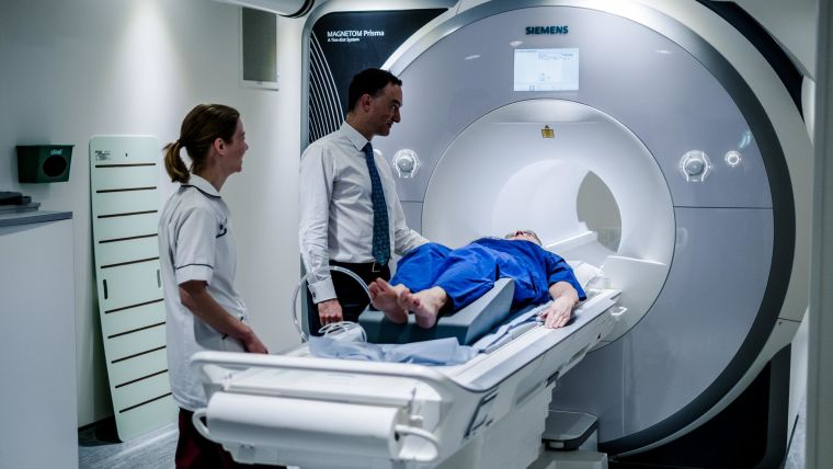 MRI scanner with patient, consultant and radiographer.