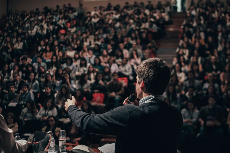 Man giving lecture to large crowd