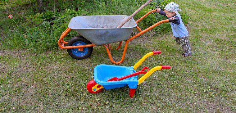Child pushing large wheelbarrow