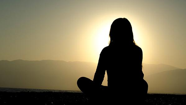 Silhouette of person sitting looking at the sunset