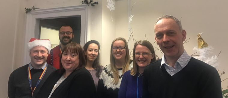 The Business Development & Partnering team standing together surrounded by festive Christmas decoration