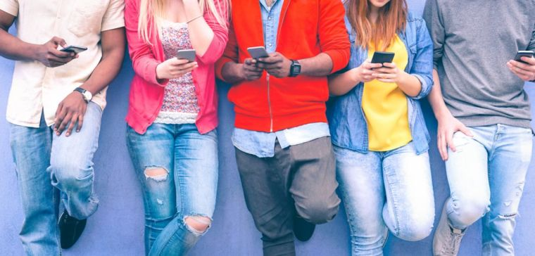 Teenagers leaning against a wall using their mobile phones