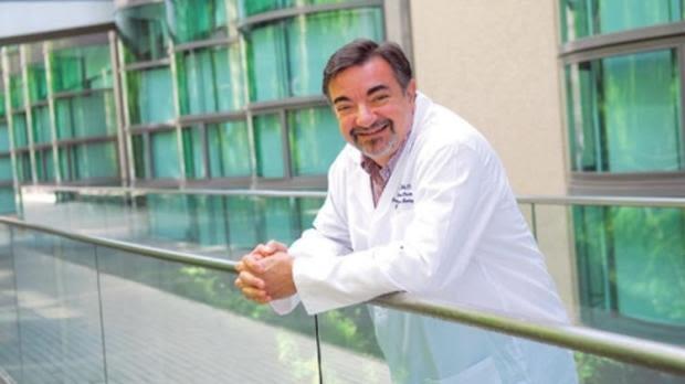 Professor Amato J Giaccia smiling in white lab coat