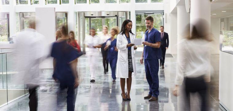 Hospital Staff In Busy Lobby Area Of Modern Hospital