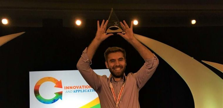 Cristian Soitu smiling, holding up his award.