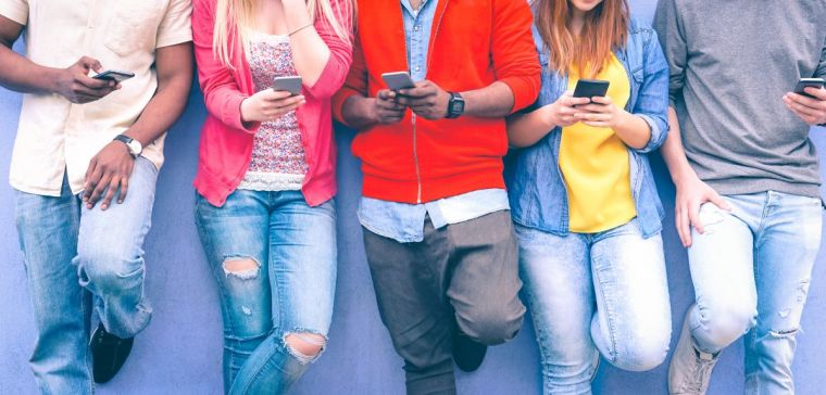 Line of teenagers leaning against a wall using their mobile phone devices