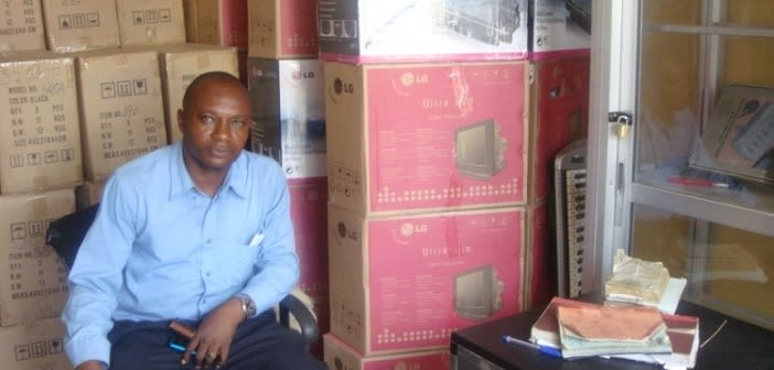 A male trader in electronics appliances at Alaba International Market, Lagos, Nigeria