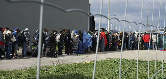 Syrian refugees line up to cross the border between Hungary and Austria