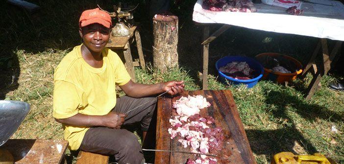 A refugee trader selling barbecued skewers of beef on market day at Juro market, Nakivale refugee settlement, Uganda