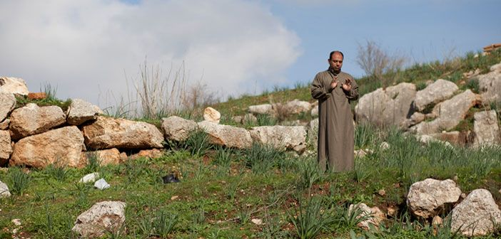 A man prays near a checkpoint on the Syrian side of the Turkish-Syrian border