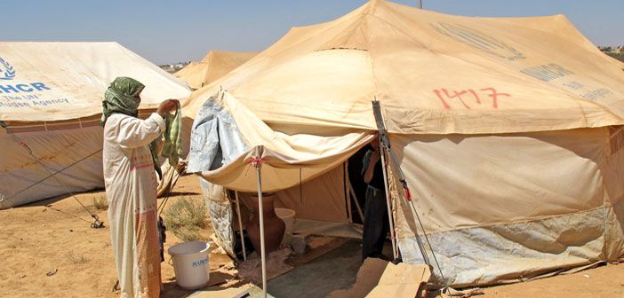 Syrian refugee woman hangs laundry in front of her tent in Za'atari camp in Jordan