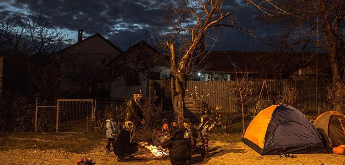 A group of Hazara refugees from Afghanistan warm themselves around a fire at the train station in Presevo, Serbia