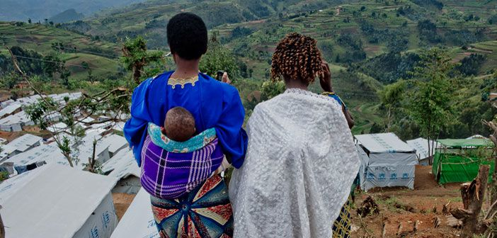 Two Congolese refugees, both members of a women's group, look at the newest section of Kigeme camp, Rwanda