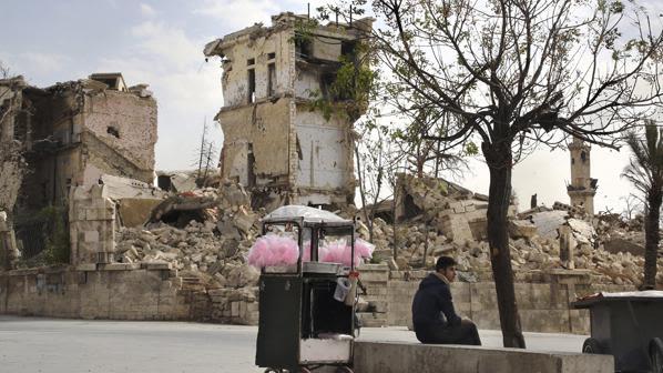 A vendor sells pink candy floss amid the ruins near the Aleppo citadel, Syria, November 2017. © UNHCR/Susan Schulman