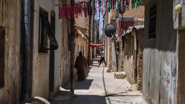 a woman walking down a narrow street in Amman