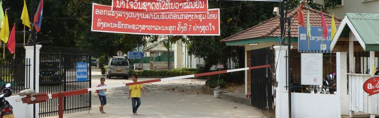 Street with large signboards in Lao language.