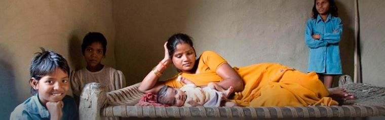 An Indian mother lying on a bed with a baby, surrounded by three children