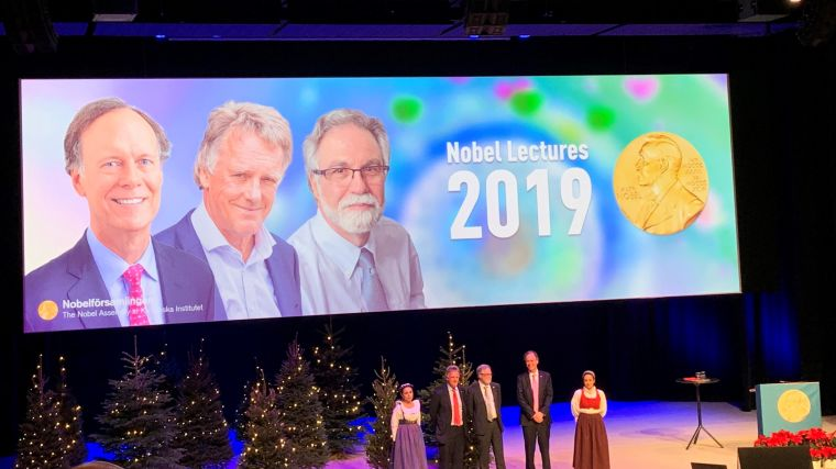 A photo from the Nobel Prize talks 2019 showing the three nominees for Medicine or Physiology on the stage.